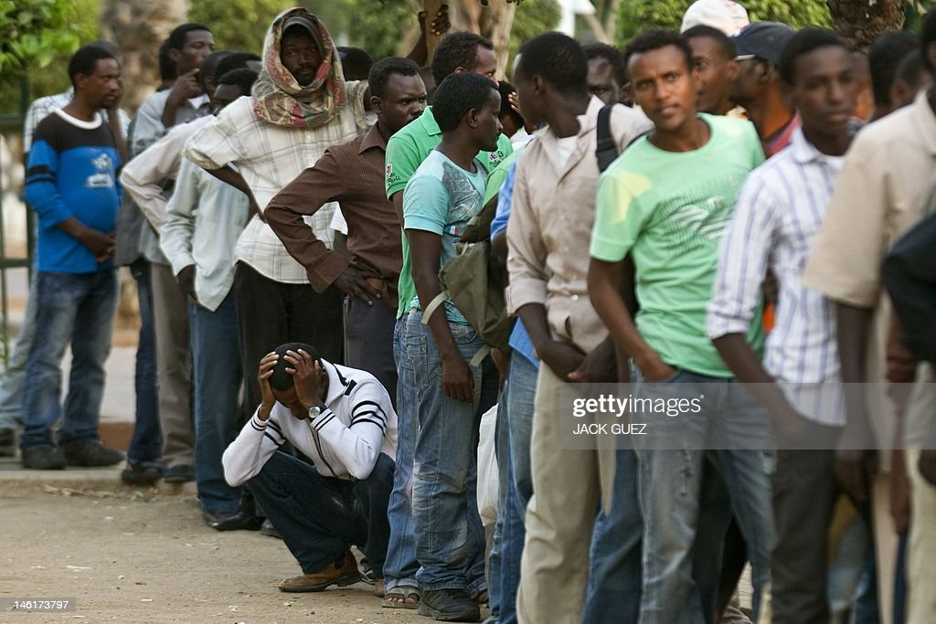African migrants line up to receive a fr : News Photo