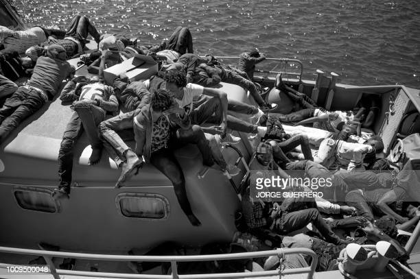 African migrants rescued in the open sea wait for being transferred after arriving onboard a coast guard boat at the harbour of Algeciras on August 1...