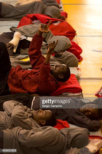 African migrants rest inside a sport center on August 13 2014 in Tarifa Spain Spain's coast guard said it picked up 920 subSaharan Africans who were...