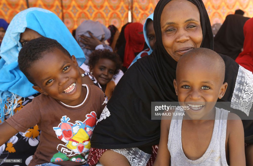 Illegal African migrants smile for the camera at an Anti-Illegal Immigration Authority shelter in Ain Zara in the Libyan capital Tripoli on July 22, 2018.