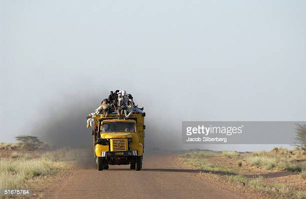 African migrants travel in the back of a truck across the Sahara Desert on September 26 2004 near Agadez Niger Thousands of migrants make the often...