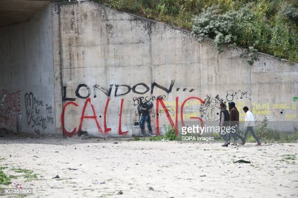 African migrants walk past the Banksy in Calais covered over by 'London calling' Thousands were living in the camp there before it was demolished The...