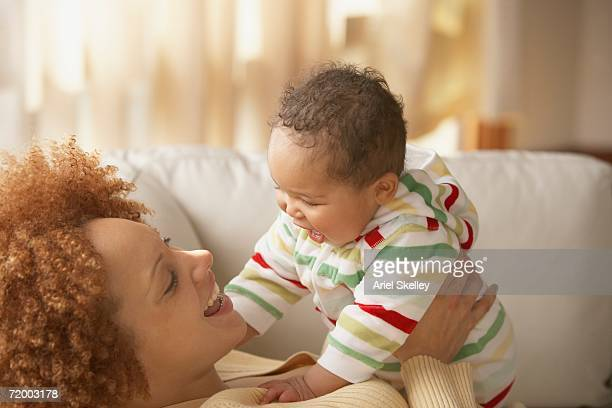 African mother and baby smiling at each other on sofa