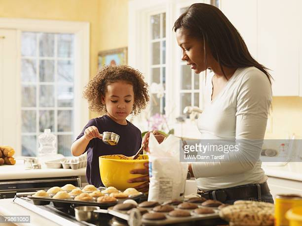 african mother and daughter baking cupcakes - measuring cup stock pictures, royalty-free photos & images