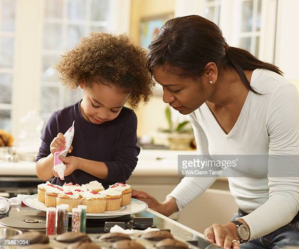 african mother and daughter decorating cupcakes - decorating a cake stock pictures, royalty-free photos & images