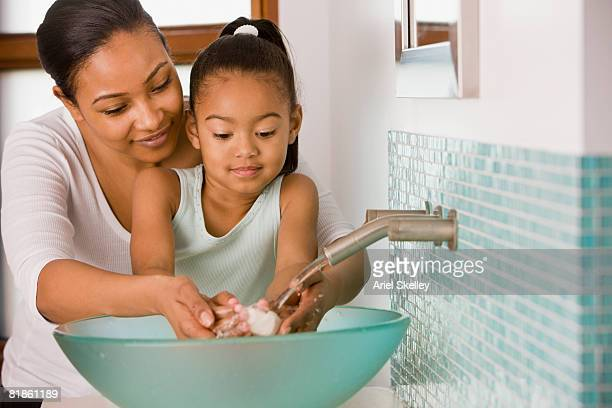 African mother and daughter washing hands