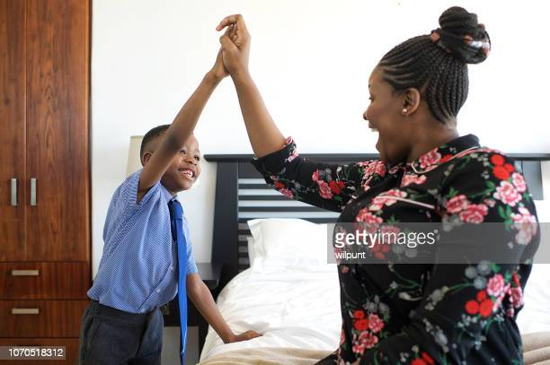 african mother and son high-five in bedroom - encouragement stock pictures, royalty-free photos & images