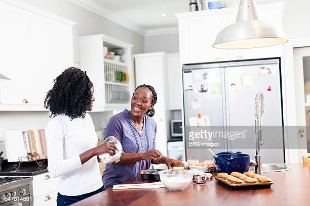 African mother and teenaged daughter baking together, daughter wiping bowl , Cape Town, South Africa