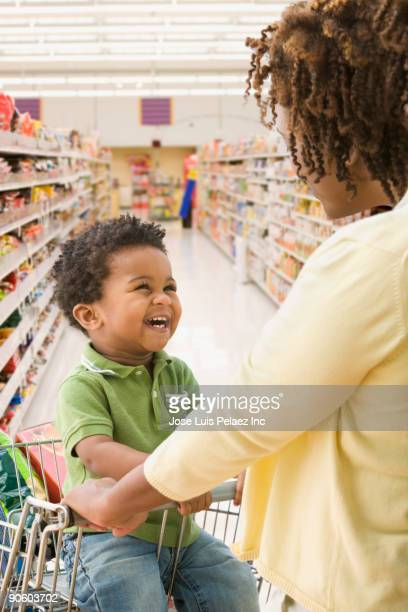 African mother and toddler shopping in grocery store