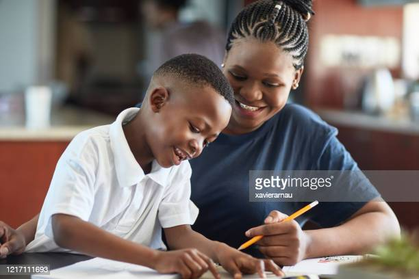 african mother and young son spending creative time together - homeschool stock pictures, royalty-free photos & images