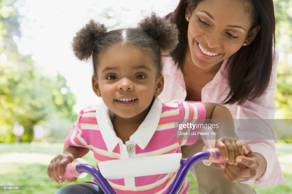 African mother helping daughter ride tricycle : Stock Photo