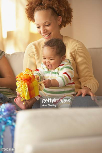 african mother holding baby and gift - black ginger baby stock photos and pictures
