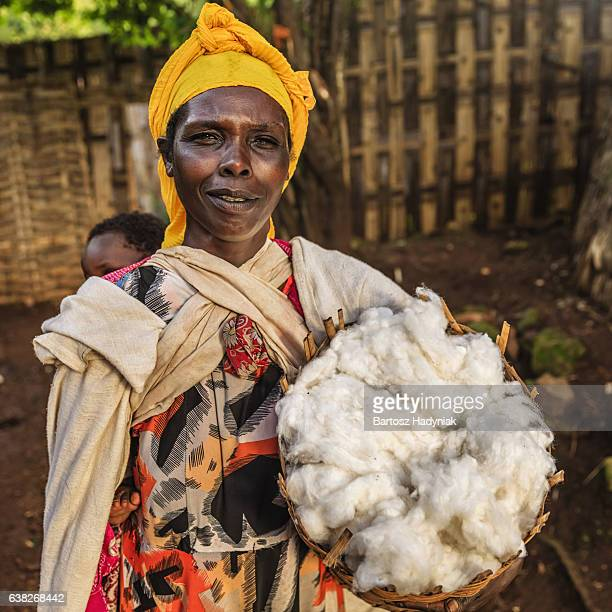 African mother holding basket of wool, East Africa