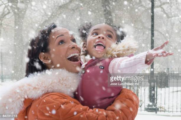 African mother holding daughter in falling snow