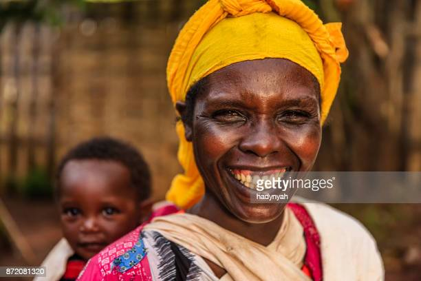 african mother holding her baby on back, east africa - village stock pictures, royalty-free photos & images