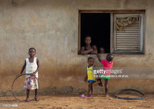 African mother looking thru her window house her children playing Région des Lacs Bomizanbo Ivory Coast on May 8 2019 in Bomizanbo Ivory Coast
