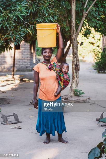 African Mother with Baby Son and water bin at Home