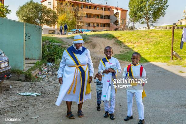 african mother with three children dressed for church in alexandra township, johannesburg - gauteng province stock pictures, royalty-free photos & images