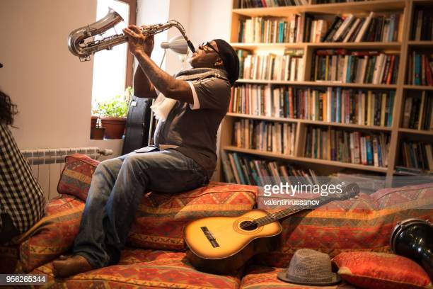 african musician playing saxophone - soloist stock photos and pictures