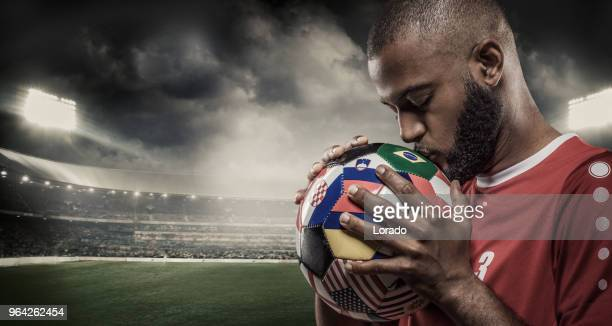 african muslim nicht-kaukasischen-football-spieler mit einer fahne bedeckt fußball in einem stadion mit flutlicht - mannschaftskapitän stock-fotos und bilder