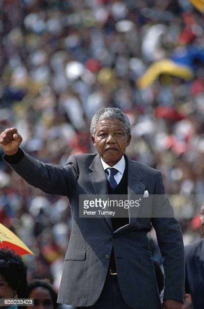 African National Congress leader Nelson Mandela raises his fist after he speaks to a crowded stadium in Soweto after his release from prison