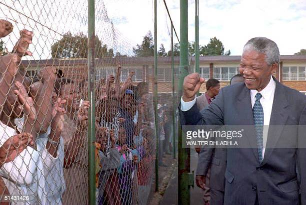 African National Congress President Nelson Mandela greets supporters behind the fence in a mining town of Randfontein west of Johannesburg 25...