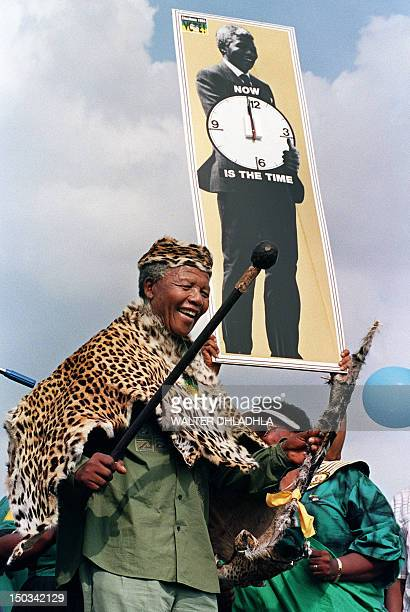 African National Congress President Nelson Mandela wearing leopard skin traditional clothes salutes the crowd 21 March 1994 at a rally to commemorate...