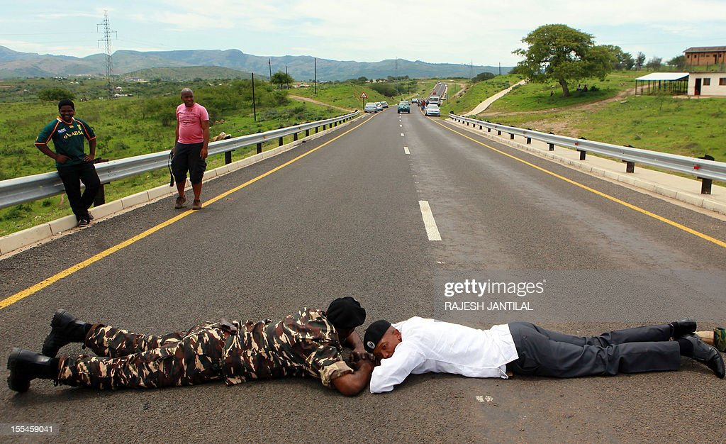 African National Congress (ANC) supporters block the road to President Jacob Zuma's private rural residence, to prevent opposition leader Hellen Zille to visit him, at the centre of a row over a $29-million state-funded upgrade in Nkandla some 178 kilometres north of Durban on November 4, 2012. Police cited safety reasons for denying Zille and her six-member delegation passage to Zuma's homestead, where they wanted to inspect how public money was used to fund the president's private property.