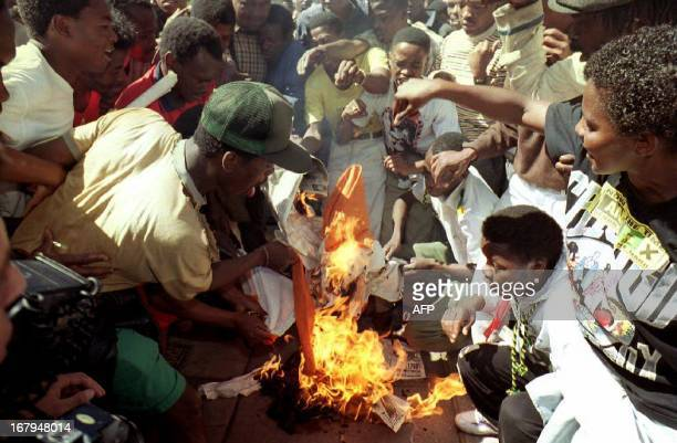 African National Congress supporters set a South African flag on fire 14 April 1993 during a commemoration service for South African Communist Party...
