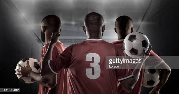 3 afrikaanse non-kaukasische voetbal spelers houden een voetbal voor stadion verlichting - internationaal voetbalevenement stockfoto's en -beelden