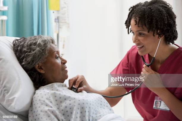 african nurse using stethoscope on hospital patient - human heart stock pictures, royalty-free photos & images