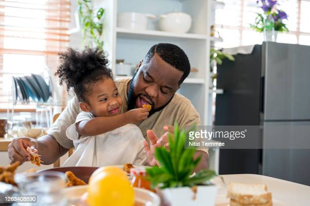 african papa and daughter having lunch together.  they are enjoy eating a fired chicken meal at home. - lunch stock pictures, royalty-free photos & images