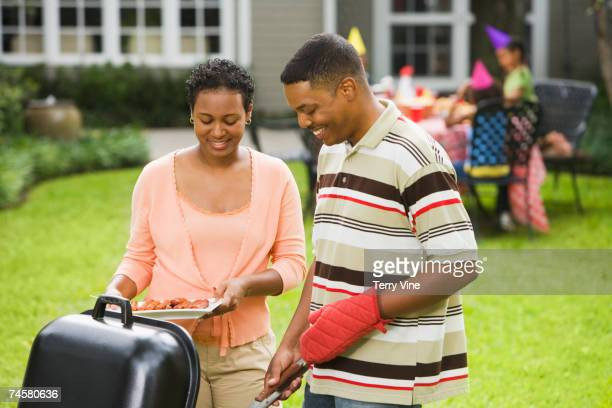 African parents barbequing for child's birthday