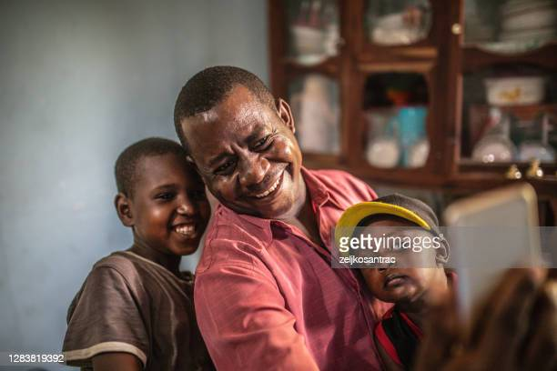 african parents helping children with homework - east africa stock pictures, royalty-free photos & images