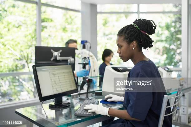 técnico de patología africana trabajando en computación en laboratorio - laboratorio clinico fotografías e imágenes de stock