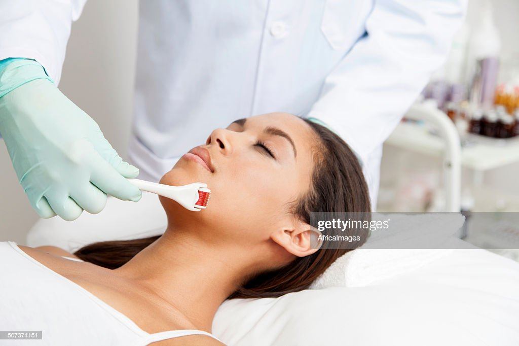African patient getting micro-needling treatment by her doctor : Stock Photo