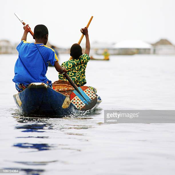 african pirogue ride. - dugout canoe stock photos and pictures