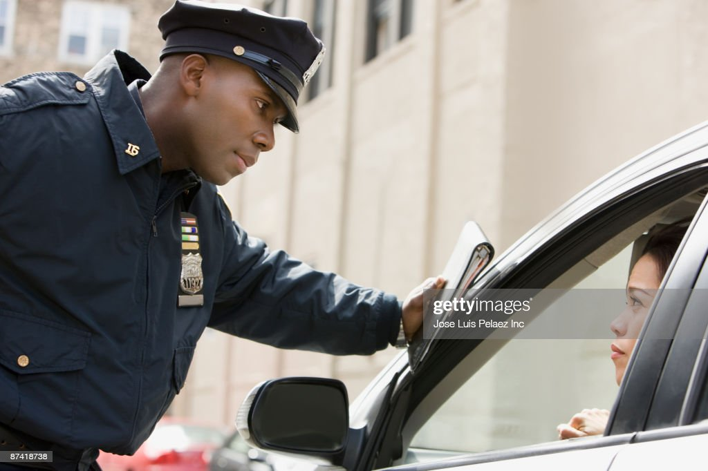 African policeman giving woman ticket : Stock Photo