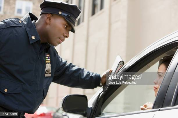 african policeman giving woman ticket - ticket stock pictures, royalty-free photos & images