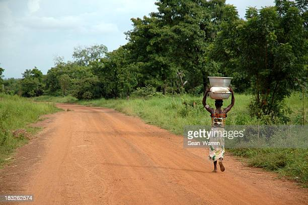 african road - woman & water - afrika stockfoto's en -beelden
