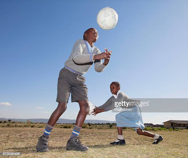 african school children (10-12) playing with balls on field - hugh sitton stock pictures, royalty-free photos & images