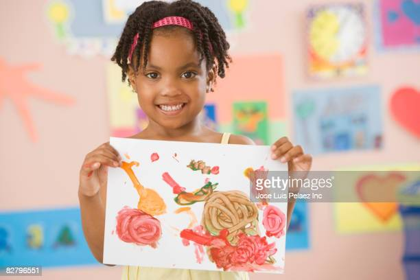 African school girl holding painting in classroom