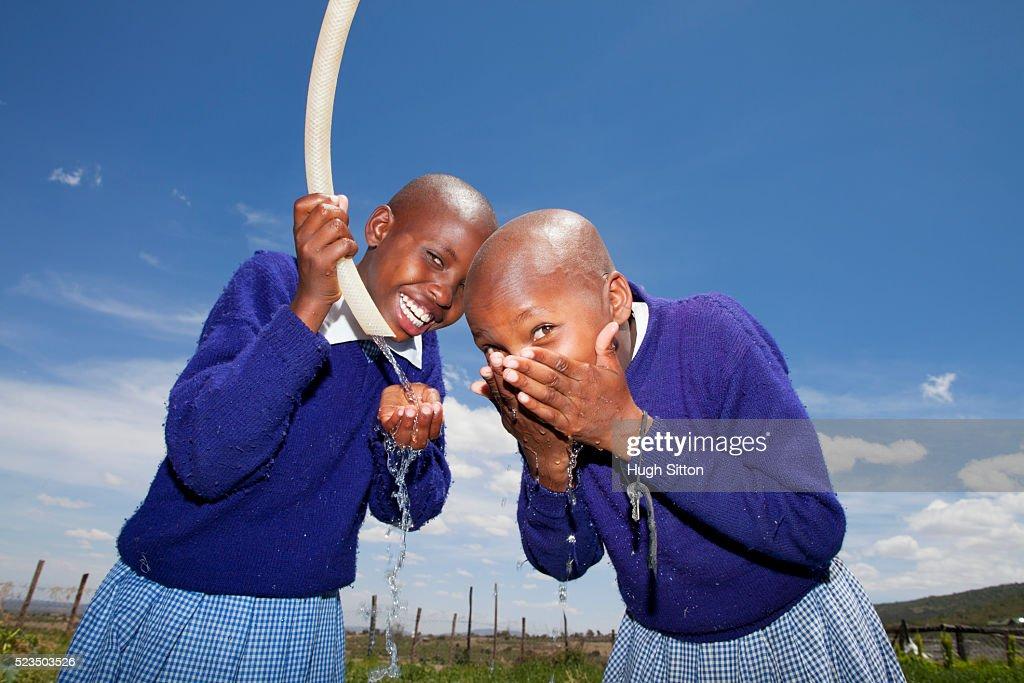 African school girls drinking water : Stock Photo