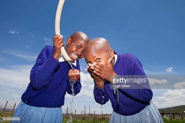 african school girls drinking water - hugh sitton stockfoto's en -beelden