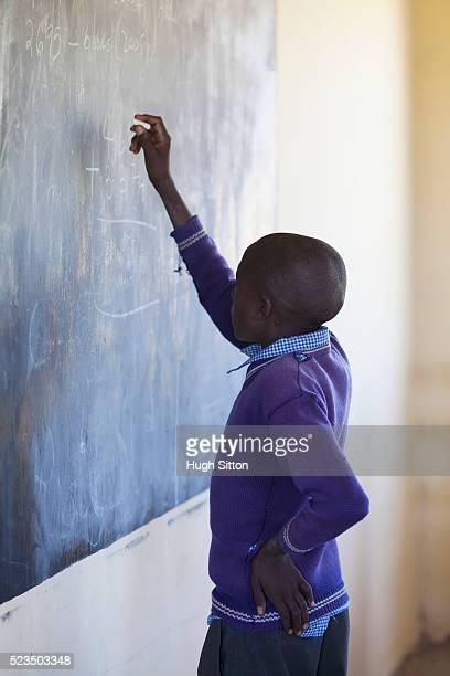 african schoolboy (10-12) in classroom writing on blackboard - hugh sitton bildbanksfoton och bilder