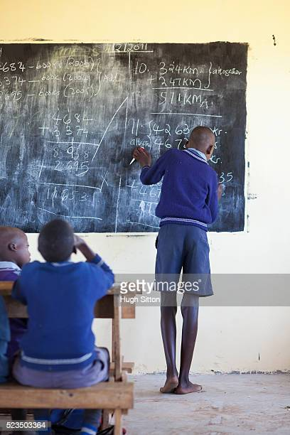 african schoolboy (10-12) in classroom writing on blackboard - hugh sitton stock-fotos und bilder