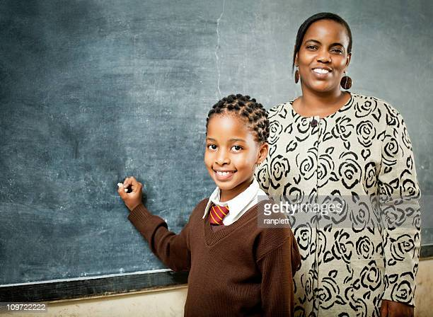 African Schoolgirl and Teacher at the Chalkboard