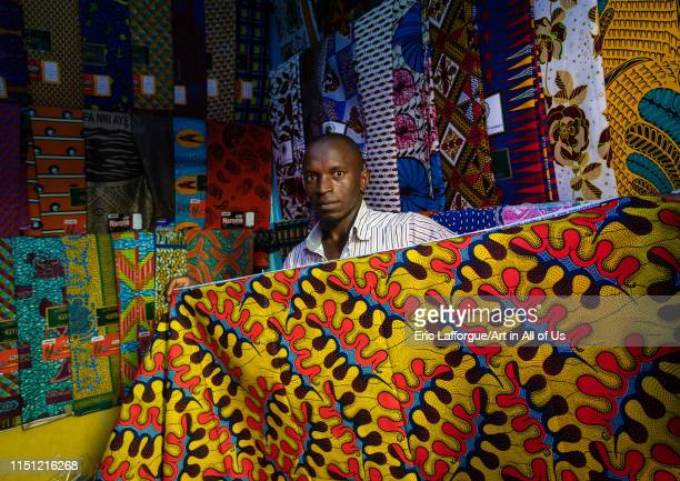 African seller with colorful african fabrics in a shop Comoé Abengourou Ivory Coast on May 9 2019 in Abengourou Ivory Coast