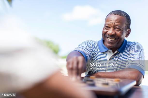 Afrikanische senior Schach spielen, die Bewegung mit einem Lächeln
