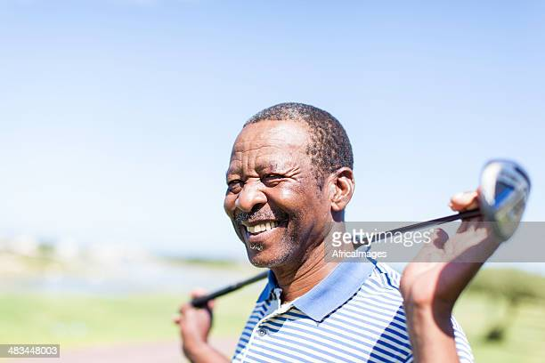 African senior golfer holding his club with a smile.